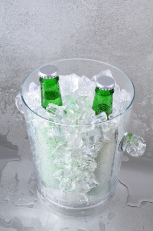 Two green beer bottles in a crystal ice bucket sitting on a wet stainless steel surface. Vertical Format with shallow depth of field. photo