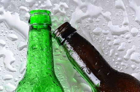 2 objects: Closeup of two beer bottles on a wet stainless steel surface. One bottle is green the other brown. The brown bottle is at an angle. Overhead view.