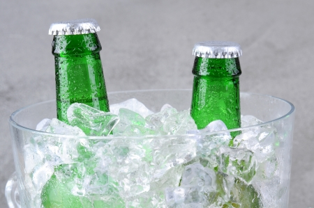 chiller: Closeup of two green beer bottles in a crystal ice bucket. Horizontal format on a gray mottled background. Stock Photo