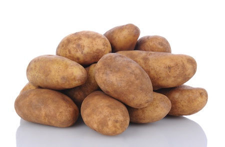 russet: Closeup of a pile of russet potatoes on a white surface with reflection. Horizontal format.