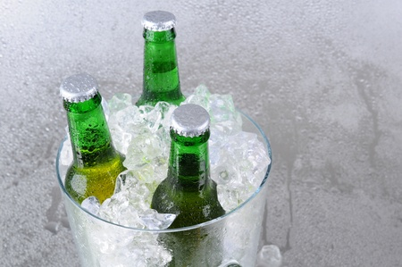 Three green beer bottles in a crystal ice bucket. High angle with copy space to the right side. Horizontal format. Stock Photo - 16460112