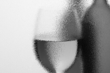 monotone: Wine Bottles and Wineglass seen in monotone through a textured window with backlight. Horizontal composition with copyspace.
