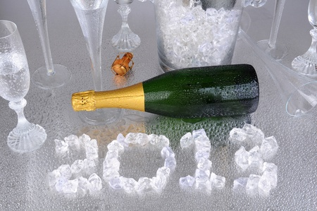 Happy New Years. 2013 spelled out with ice cubes on a wet metallic surface, surrounded by a champagne bottle, and flutes. photo