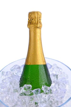 Closeup of a Champagne bottle in a crystal ice bucket. Vertical format over a white background. Banco de Imagens