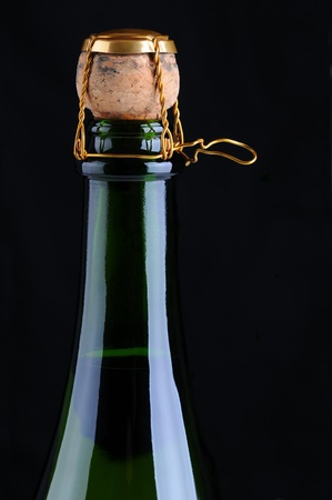 champagne cork: Closeup of a champagne bottle with cork and cage on a black background. Vertical Format.