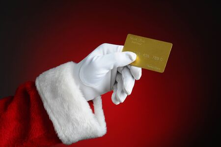 Santa Claus hand holding a gold credit card over a light to dark red background. Horizontal format showing hand and arm only.