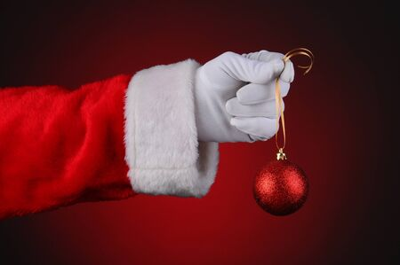 Santa Claus hand holding a sparkly red ornament on a gold ribbon over a light to dark red background. Horizontal format hand and arm only. Stock Photo - 16581996