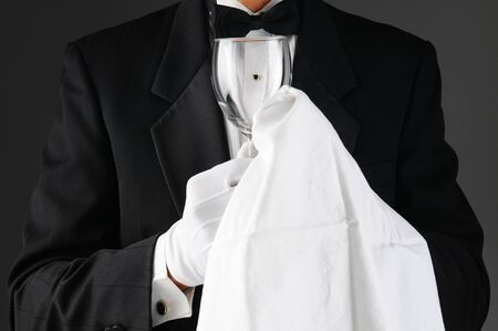 polishing: Closeup of a waiter wearing a tuxedo polishing a wine glass. Horizontal format on a light to dark gray background. Man is unrecognizable.