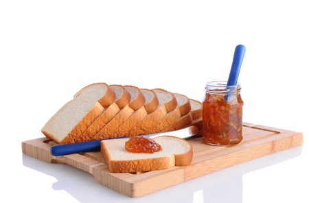 Closeup of bread on a cutting board with orange marmalade. Horizontal format on a white background with reflection. One slice has a dollop of jam on it. Stock Photo - 16581994