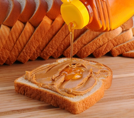 pb: Closeup of making a peanut butter and honey sandwich. Slice of bread with PB  already spread and honey being poured on. Shallow Depth of field with slices of bread in the background.