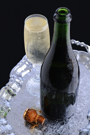party tray: Closeup of a champagne bottle and flute on a silver tray. Cork and cage tray are also on the tray. Vertical format with a black background.