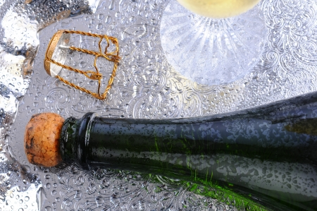 Closeup of a champagne bottle laying on its side on a silver tray. Cork cage and out of focus flute are also on the tray. Horizontal format. Standard-Bild