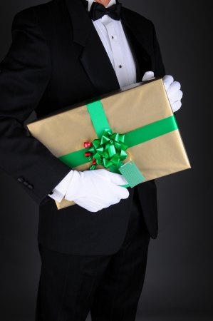 Closeup of a gentleman in a tuxedo holding a Christmas present under his arm. Vertical format on a light to dark gray background. Man is unrecognizable. photo