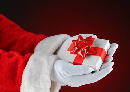 Santa Claus holding a small Christmas Present in both of his hands. Horizontal format showing only hand and arms on a light ot dark red background. Stock Photo - 16747097