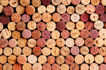 corcho: Primer plano de una pared de corchos de vino usados. Una selección aleatoria de corchos de vino uso, algunos con años de cosecha. Formato horizontal que llena el marco.