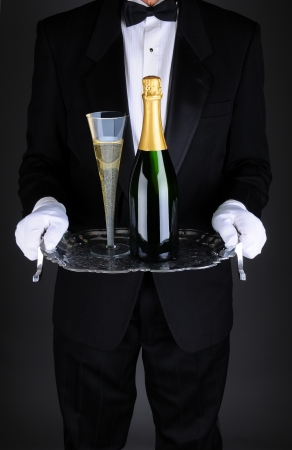 party tray: Closeup of a waiter with a bottle and flue of champagne on a silver serving tray. Vertical format over a light to dark gray background. Man is unrecognizable.