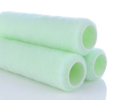 paintroller: Closeup of a stack of paint roller covers on a white background with reflection. Horizontal format.