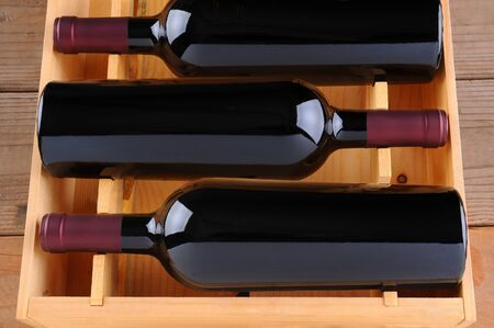 Three red wine bottles in a wooden case, isolated on white, Vertical Format. photo