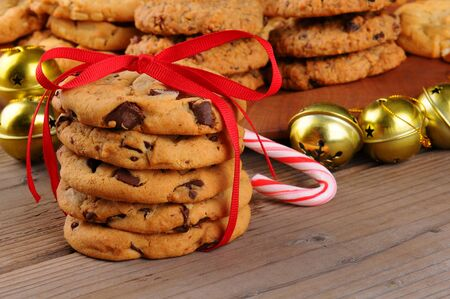 christmas sleigh: A stack of holiday chocolate chip cookies tied with a red ribbon in front of jingle bells , candy cane, and a platter of assorted baked treats. Horizontal format with shallow depth of field.