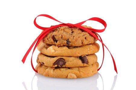 Closeup of a stack of assorted cookies tied up with a red ribbon, isolated on white. Chocolate chip, oatmeal raisin and white chocolate chip cookies are represented. photo