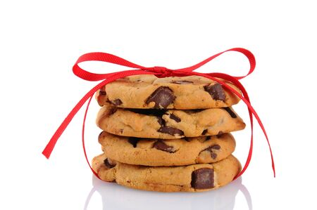 Closeup of a stack of chocolate chip cookies tied up with a red ribbon, isolated on white. photo