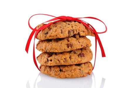 oatmeal cookie: Closeup of a stack of Oatmeal Raisin Cookies tied up with a red ribbon, isolated on white.