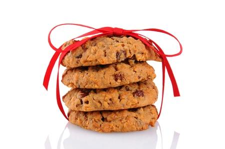 Gros plan d'une pile de biscuits à l'avoine et aux raisins attachés avec un ruban rouge, isolé sur blanc. Banque d'images - 16883970