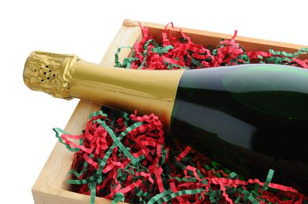 shred: Closeup of a Champagne bottle in a wood shipping crate with shredded filler paper in Christmas Holiday colors. Horizontal format isolated on a white background.