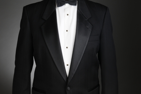 dinner wear: Closeup of a Black Tuxedo Jacket. Torso only on a light to dark gray background. Horizontal format.