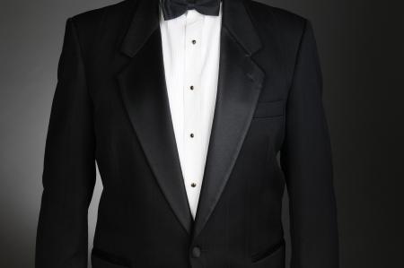 tuxedo man: Primo piano di una giacca da smoking nero. Torso solo su una luce di sfondo grigio scuro. Formato orizzontale.