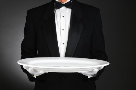 corbata negra: Camarero que sostiene una bandeja grande y blanca sobre una luz de fondo gris oscuro. Formato horizontal, el hombre es irreconocible.