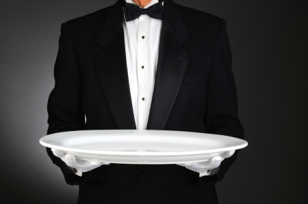 servant: Waiter holding a large white platter over a light to dark gray background. Horizontal format, man is unrecognizable.