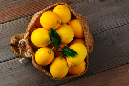Overhead view of a burlap sack filled with fresh picked lemons on a rustic wood background Stock Photo - 17182969