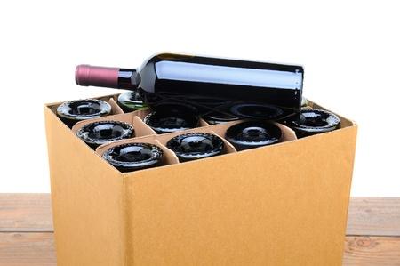 Gros plan d'une caisse de vin avec une bouteille reposant sur le dessus. Case est assis sur une table en bois avec un fond blanc. Banque d'images - 17212274