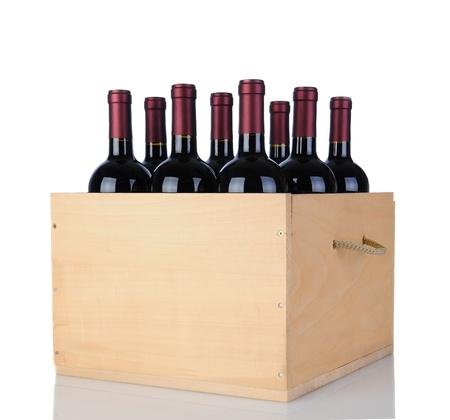 Cabernet Sauvignon bouteilles de vin dans une caisse en bois. Format vertical isolé sur blanc avec la réflexion.