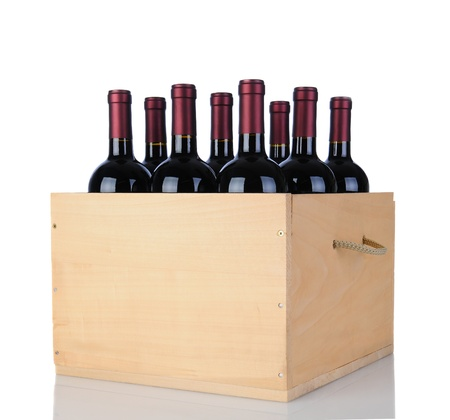 wines: Cabernet Sauvignon wine bottles in a wooden crate. Vertical format isolated on white with reflection.