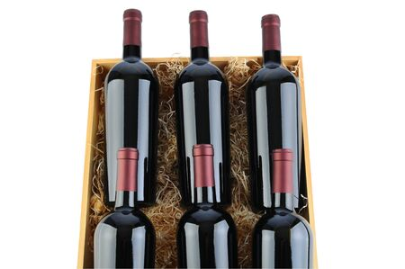 cabernet sauvignon: Closeup of six Cabernet Sauvignon wine bottles in a wooden crate with packing straw. Horizontal format isolated on white. Stock Photo