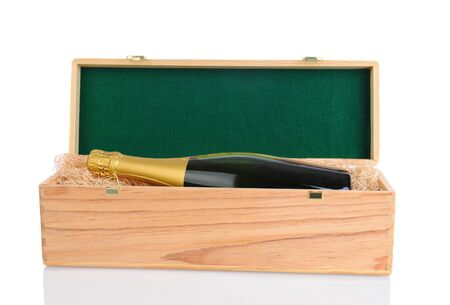 A Champagne Bottle laying inside a gift box with excelsior and lid propped open. Horizontal format over a white background with reflection. photo