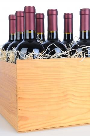 cabernet: Cabernet Sauvignon botellas de vino en una caja de madera. Formato vertical aislado en blanco con la reflexi�n.