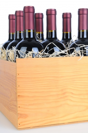 Cabernet Sauvignon wine bottles in a wooden crate. Vertical format isolated on white with reflection. photo