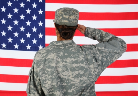 armed services: Closeup of an American Female Soldier in combat uniform saluting a flag. Seen from behind horizontal format with the flag filling the frame.