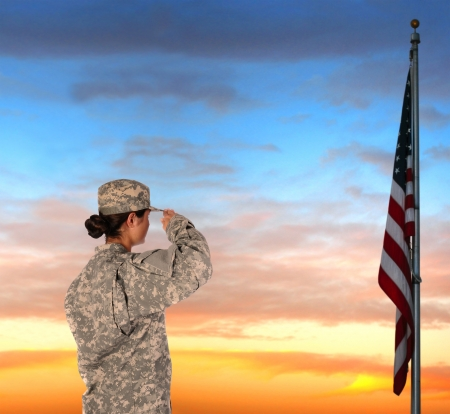 estrellas  de militares: Primer plano de un soldado americano femenino en uniforme de combate que saluda la bandera al atardecer.