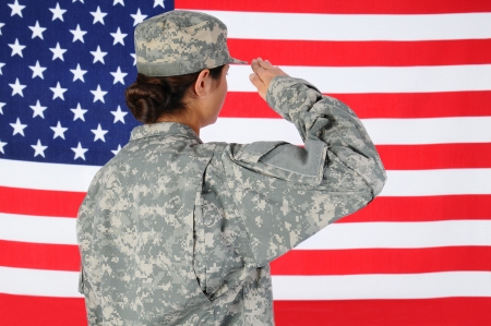 veterans day: Closeup of an American Female Soldier in combat uniform saluting a flag. Seen from behind horizontal format with the flag filling the frame.