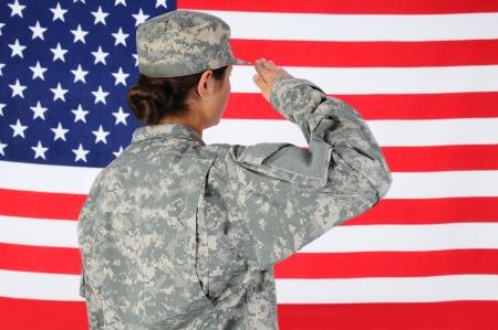 salut: Närbild av en amerikansk kvinnlig soldat i strid uniform salutera en flagga. Sett bakifrån horisontell format med flaggan fylla ramen. Stockfoto
