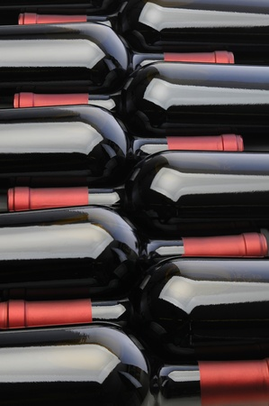 Closeup of a row of red wine bottles nested together  Vertical format fills the frame