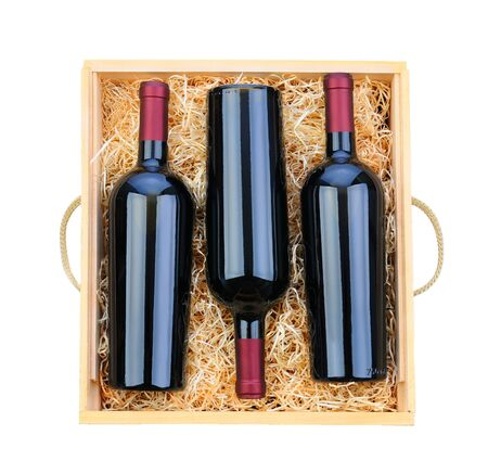 Closeup of three red wine bottles in a wooden case with packing straw  Overhead shot on a white background  Stockfoto