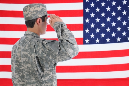 saluting: Closeup of a young American Soldier in Fatigues saluting the Flag  Flag fills the frame and is out of focus  Man is seen from behind