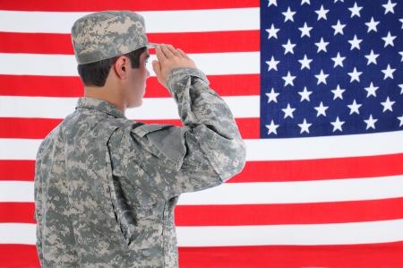 salut: Närbild på en ung amerikansk soldat i tröttar ut salutera flaggan flagga fyller ramen och är ur fokus Människan ses bakifrån