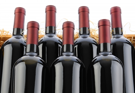 beverage display: Closeup of seven Cabernet Sauvignon Wine Bottles in Crate with Straw on a white background.