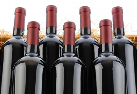 Gros plan de bouteilles de Cabernet Sauvignon Vin de sept Crate avec la paille sur un fond blanc. Banque d'images - 17585404